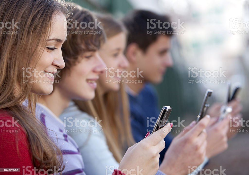 Young men and women holding mobile phones royalty-free stock photo
