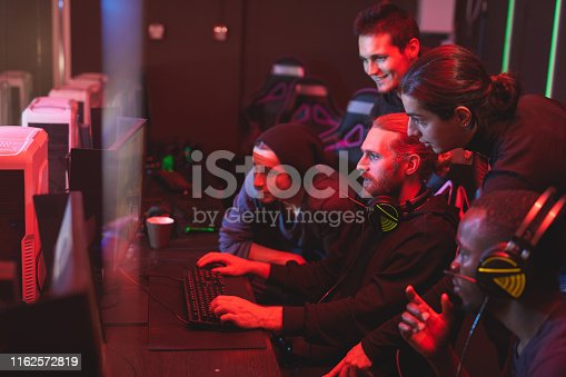 Group of focused young men standing together in front of computer monitor and playing video game, friends assisting guy to pass network game