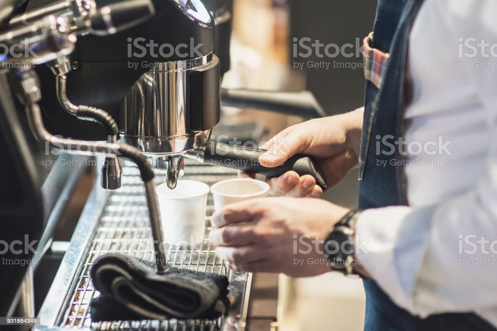 Young men barista at work in a cafe. Preparing coffee stock photo