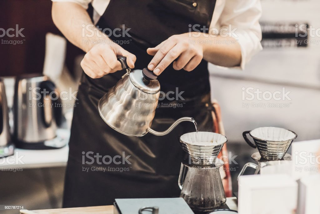 Young men barista at work in a cafe. Preparing pour over coffee stock photo