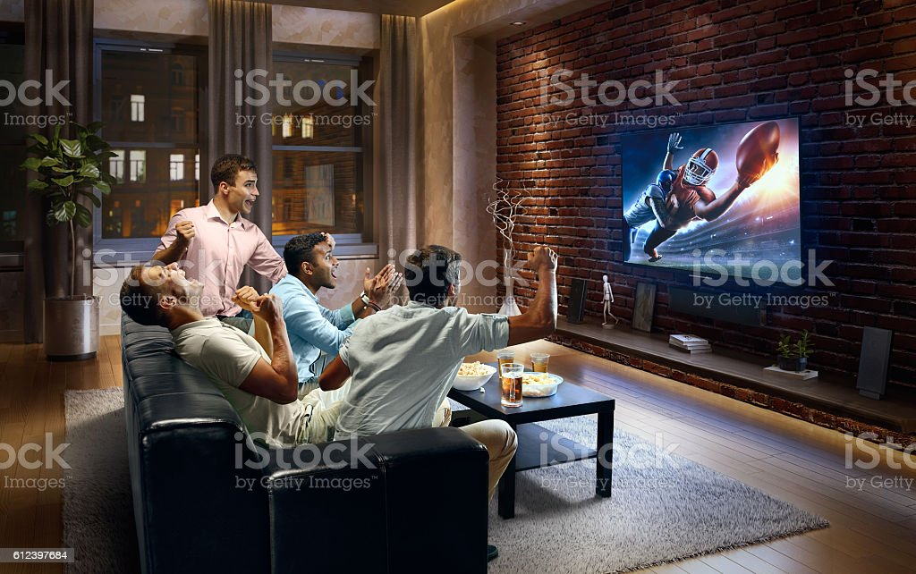 Young men cheering and watching American football game on TV stock photo