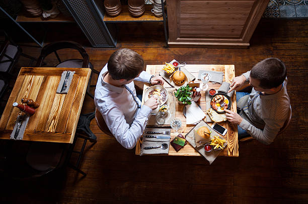 Young men eating out in cafe or restaurant stock photo