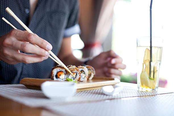 junger mann essen sushi - sushi essen stock-fotos und bilder
