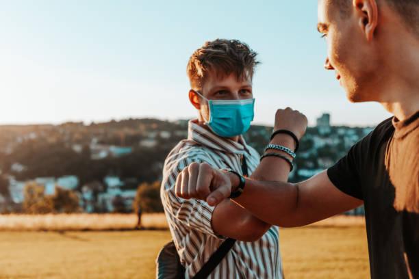 Young Men Elbow Bump wearing Corona Virus Protective Face Masks stock photo