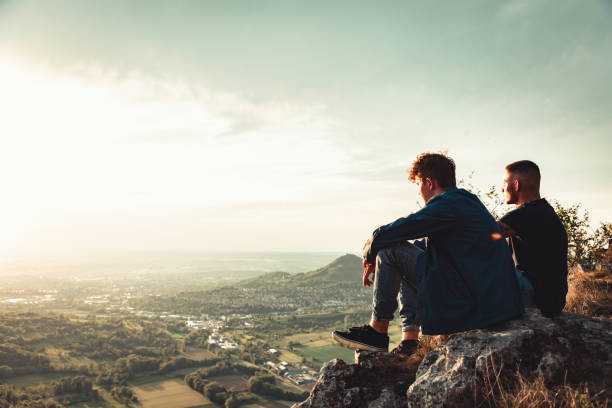 Young Men enjoying the Sunset View on Mountain Top Together stock photo