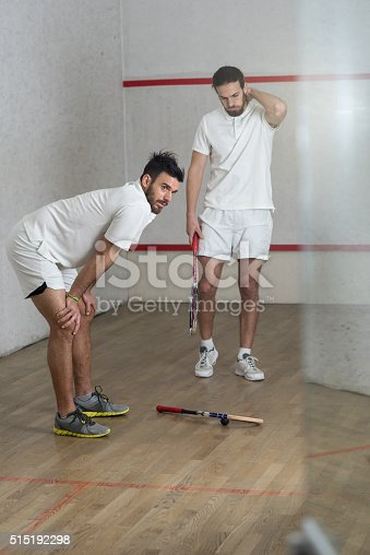 Two athletic man resting after a racketball game on a court. Focus is on man leaning on his knees.