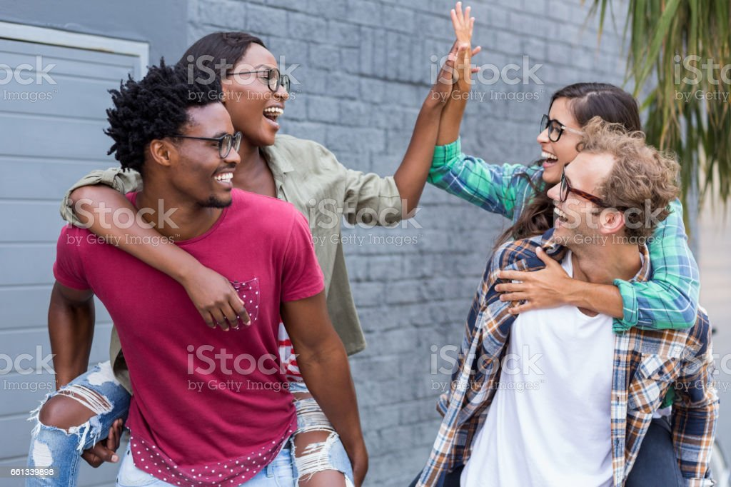 Young men giving piggyback to women stock photo