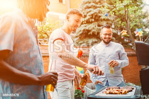 istock Young Men Grilling Meat At Barbecue Party. 488483478