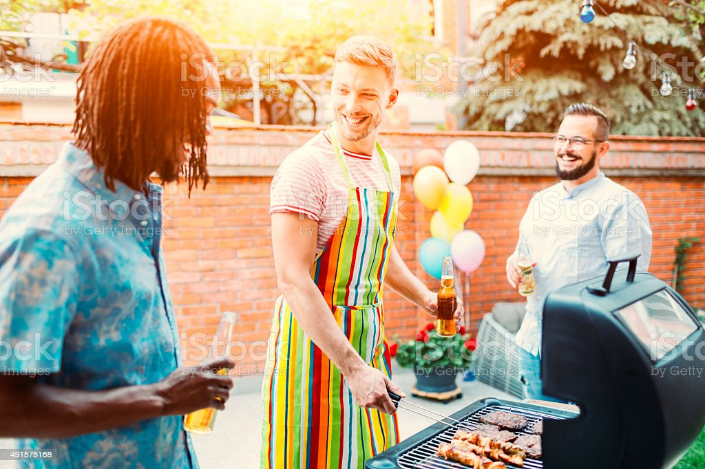 Young Men Grilling Meat At Barbecue Party.​​​ foto