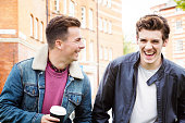 Young men having a good laugh while commuting on foot. Shot in London, UK.