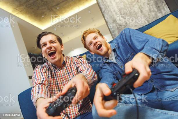 Young men having party indoors fun together playing sports game on picture id1193614264?b=1&k=6&m=1193614264&s=612x612&h=7eekb9xxsxnojr8kdpfciu8b absaquwazx7fqexzpg=
