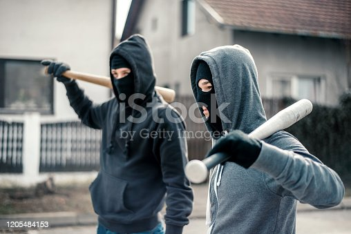 Young men holding a baseball bat symbolizing crime