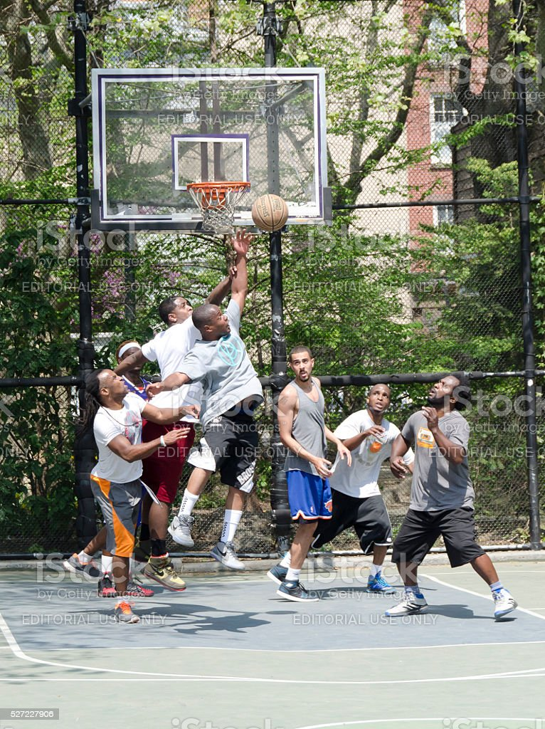 young men in action playing basketball in the street stock photo