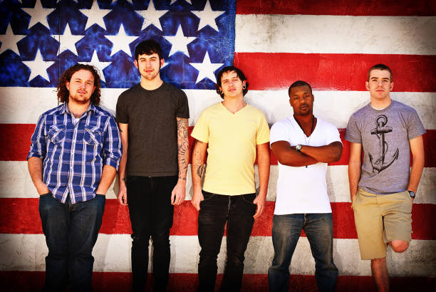 Young Men in Front of American Flag  american flag tattoos for men stock pictures, royalty-free photos & images