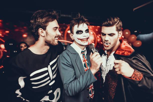 junge männer in halloween-kostümen, die karaoke singen - faschingskostüme herren stock-fotos und bilder