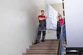istock Young Men In Uniform Carrying Mattress Downward 1180605603