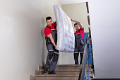 istock Young Men In Uniform Carrying Mattress Downward 1180605611