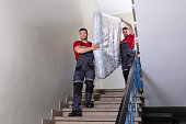 istock Young Men In Uniform Carrying Mattress Downward 1180605635