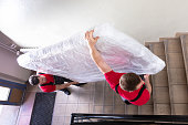 istock Young Men In Uniform Carrying Mattress Downward 1180605637