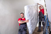 istock Young Men In Uniform Carrying Mattress Downward 1180605646