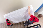 istock Young Men In Uniform Carrying Mattress Downward 1180605703