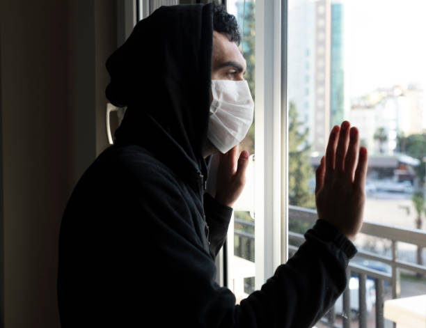 young men isolated himself wearing a face mask quarantine himself - hand on glass covid foto e immagini stock