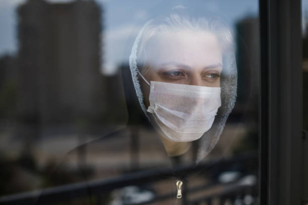 young men isolated himself wearing a face mask quarantine himself looking outside behind the window - hand on glass covid foto e immagini stock