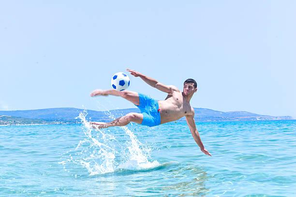 homens jovens fazendo uma atração acrobática chute a bola no mar - futebol de areia - fotografias e filmes do acervo