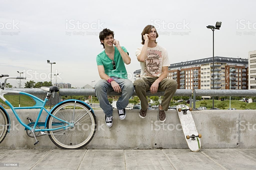 Young men on cellphones stock photo