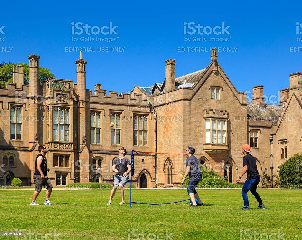 young men playing Sepak Takraw (kick volleyball) on the lawn. stock photo