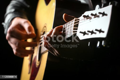 Young men playing the guitar with black background