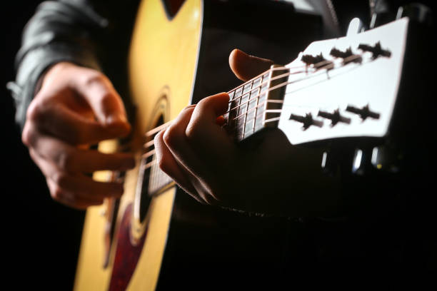 Young men playing the guitar with black background Young men playing the guitar with black background string instrument stock pictures, royalty-free photos & images