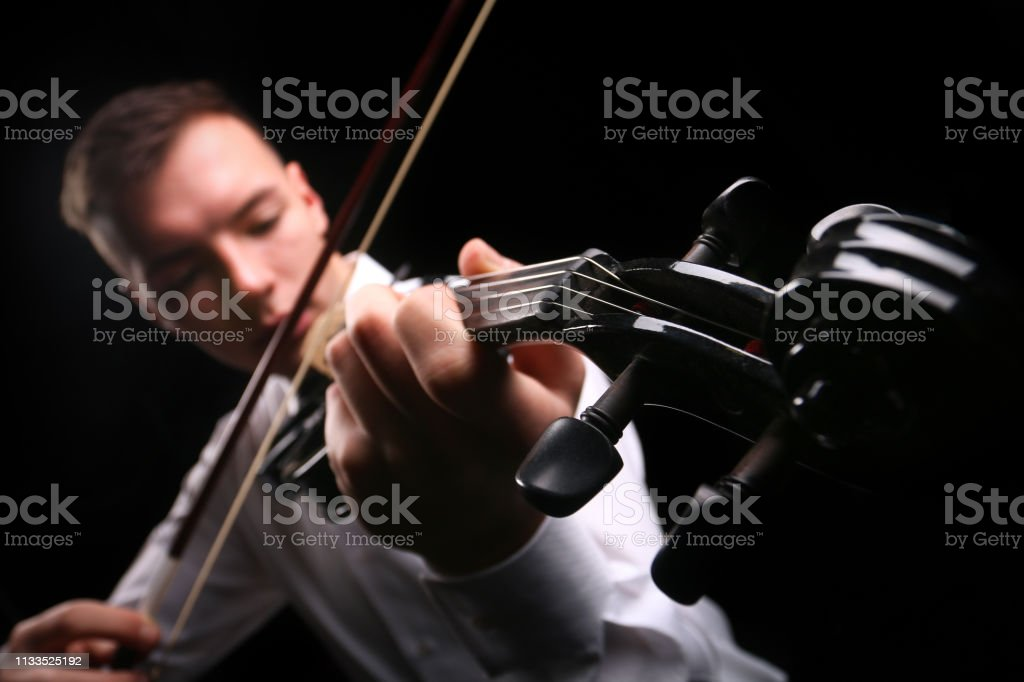 Young men playing the violin with black background stock photo