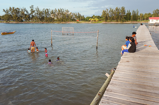 Kota Kinabalu / Malaysia - January 13, 2019: young men playing volleyball during high tide in floating village in Sabah