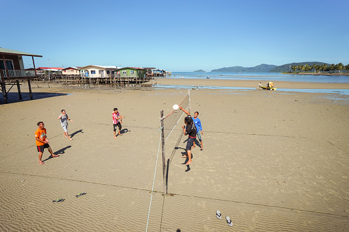 Kota Kinabalu / Malaysia - January 13, 2019: young men playing volleyball in the beach next to floating village during low tide