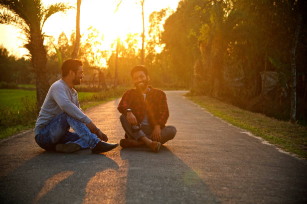 Young men sitting and smiling around an empty road stock photo