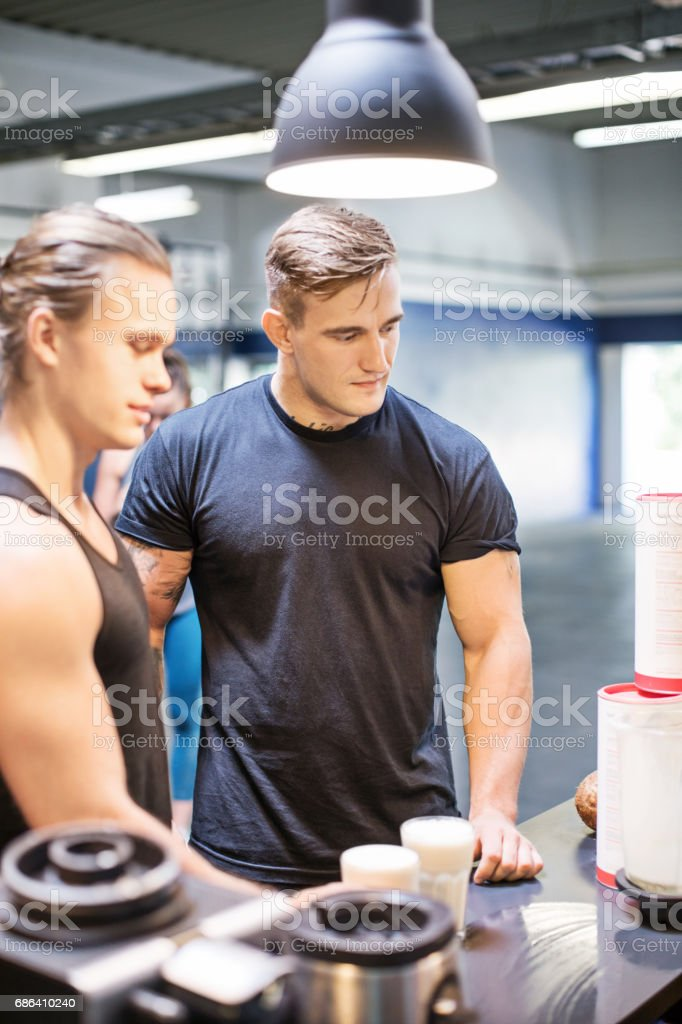 Young men standing at cafe in gym stock photo