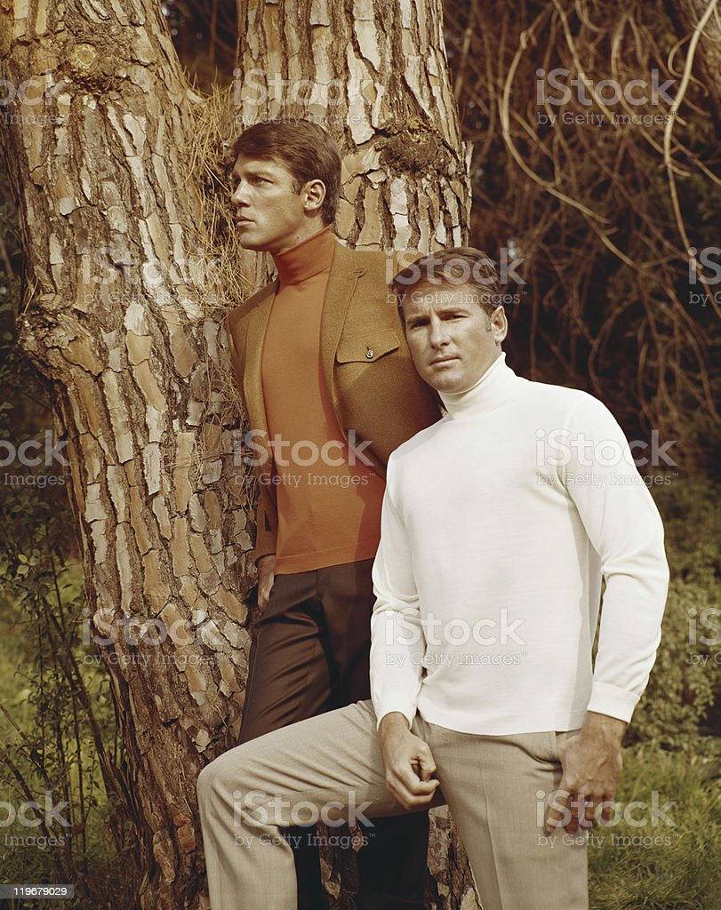 Young men standing besides tree stock photo