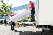 istock Young Men Unloading The Mattress From Truck On Street 1180605668