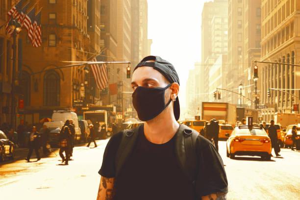 若い男性はニューヨークでマスクを持って歩く - corona newyork ストックフォトと画像