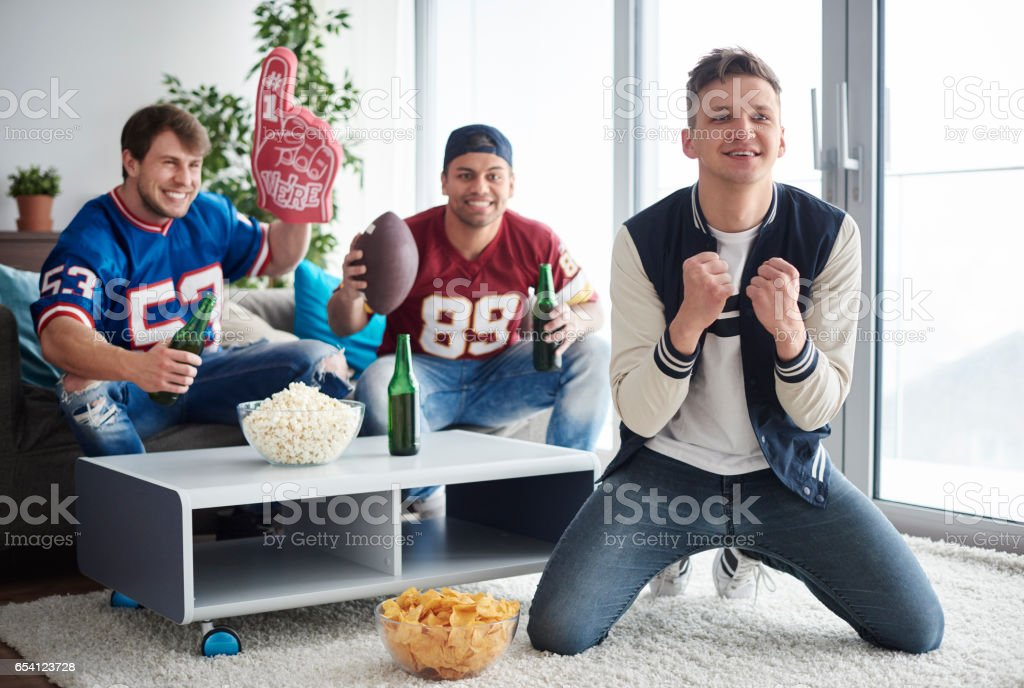 Young men watching American football competition stock photo
