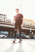 Young Men with his skateboard moving in the city