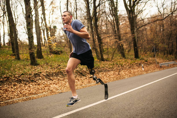 Young men with prosthetic legs running in the forrest Young male with amputee right leg running in the woods/forrest in autumn paraplegic stock pictures, royalty-free photos & images