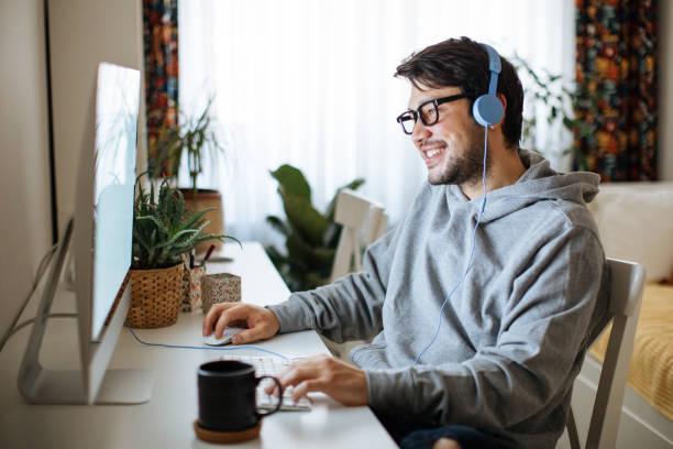 自宅で働く若い男性 - ゲーム ヘッドフォン ストックフォトと画像