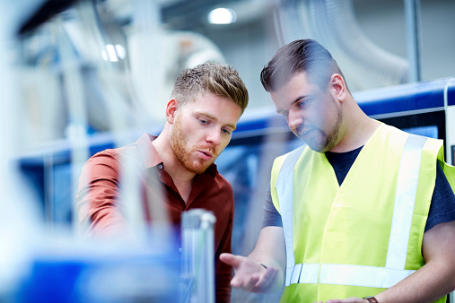Young manager and foreman looking at machine on production line