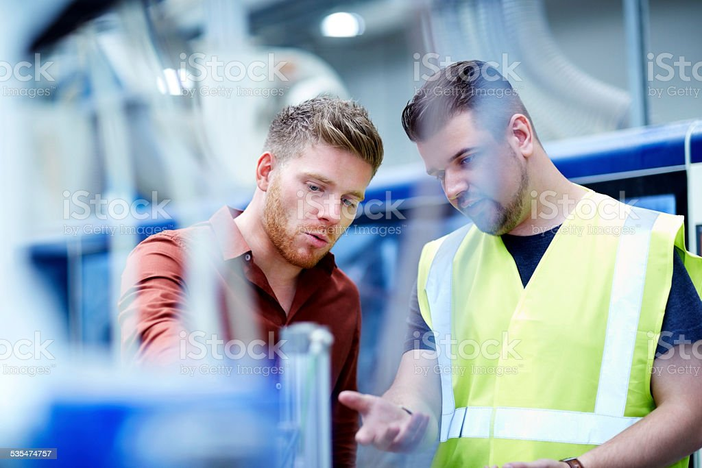 Young men working in manufacturing facility stock photo