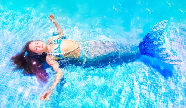 junge meerjungfrau schwimmen im pool mit geschlossenen augen - meerjungfrau kleid stock-fotos und bilder