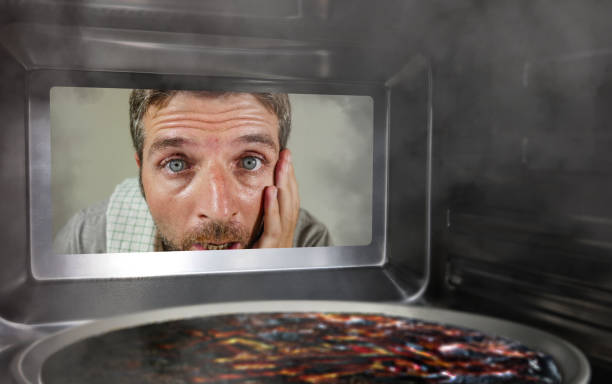 young messy and funny dummy man in the kitchen looking through microwave or oven pizza burning overcooked making a mess of home cook in domestic disaster and lifestyle concept - burned oven imagens e fotografias de stock