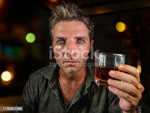 young messy and wasted man drunk at night club or bar drinking whiskey glass looking hammered celebrating party or suffering alcoholism problem and alcohol addiction