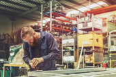 istock Young Metal Worker Using Power Tool In Factory With Protective Equipment 933344826